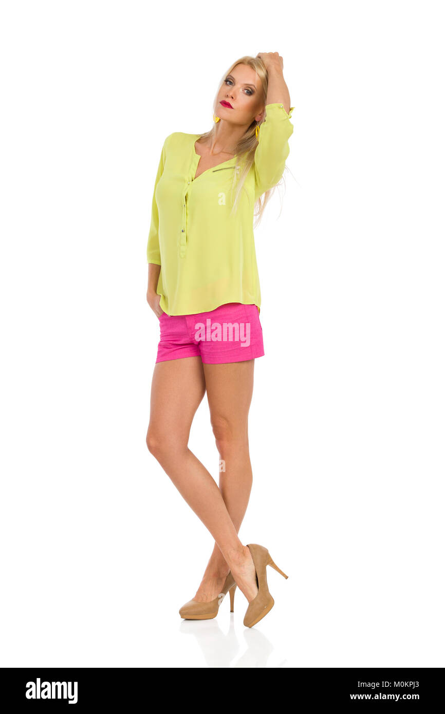 Serious beautiful blond woman in pink shorts, yellow shirt and high heels is standing legs crossed and looking at - Stock Image