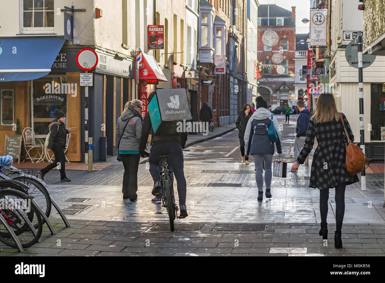 Deliveroo employee on a push bike delivering fast food with a delivery box on his back in Cork City, Ireland - Stock Image