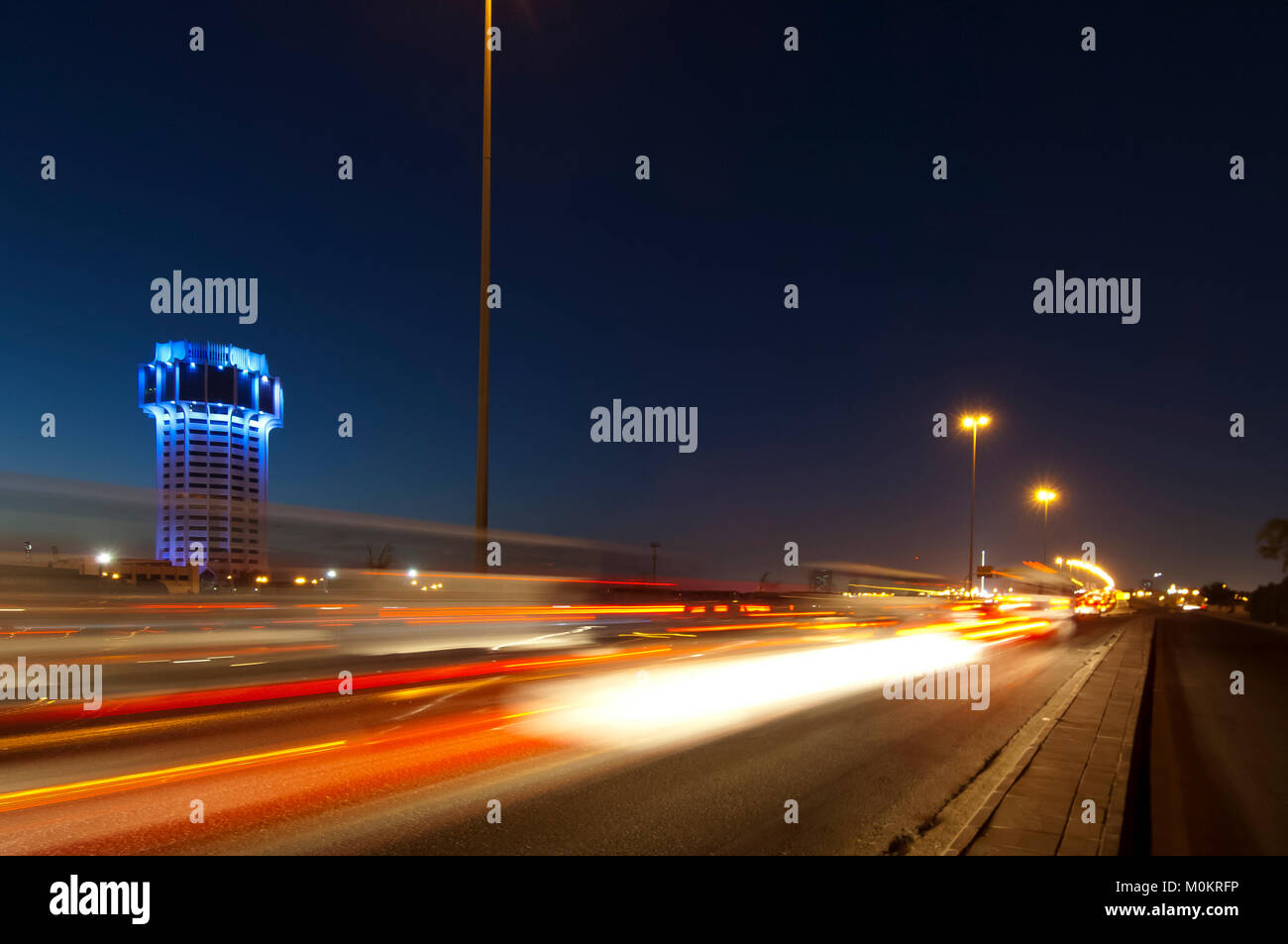 Jeddah water tower at night, with car lights motion on the street