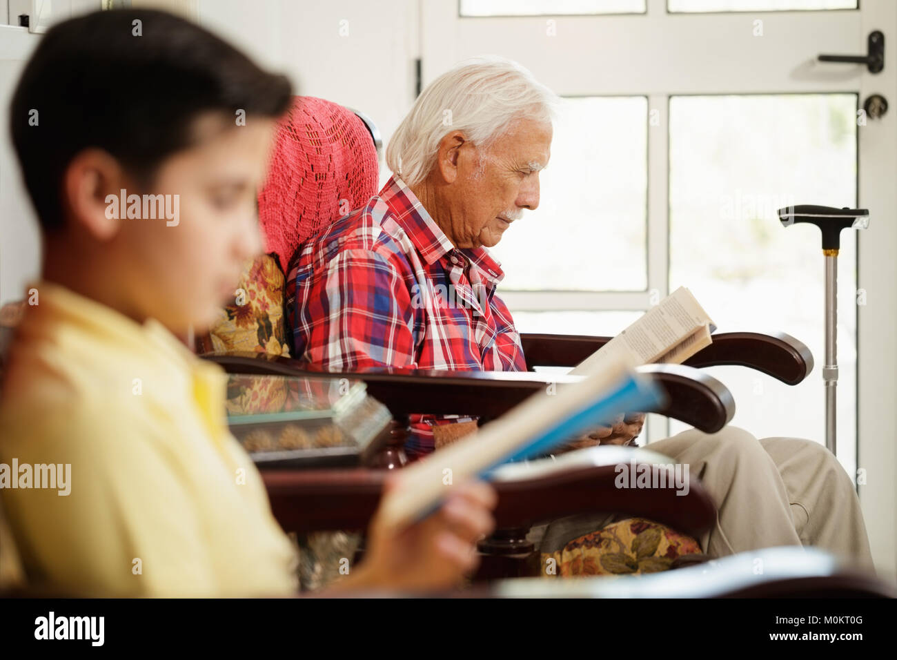 Grandson And Grandpa Reading Book And Relaxing At Home - Stock Image