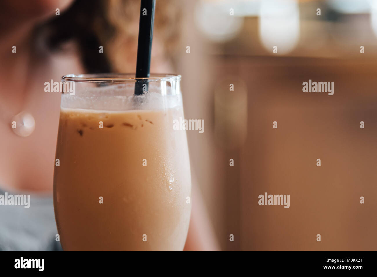 Close up of Girl Drinking a Milkshake with Space for Copy. Focus on milkshake - Stock Image