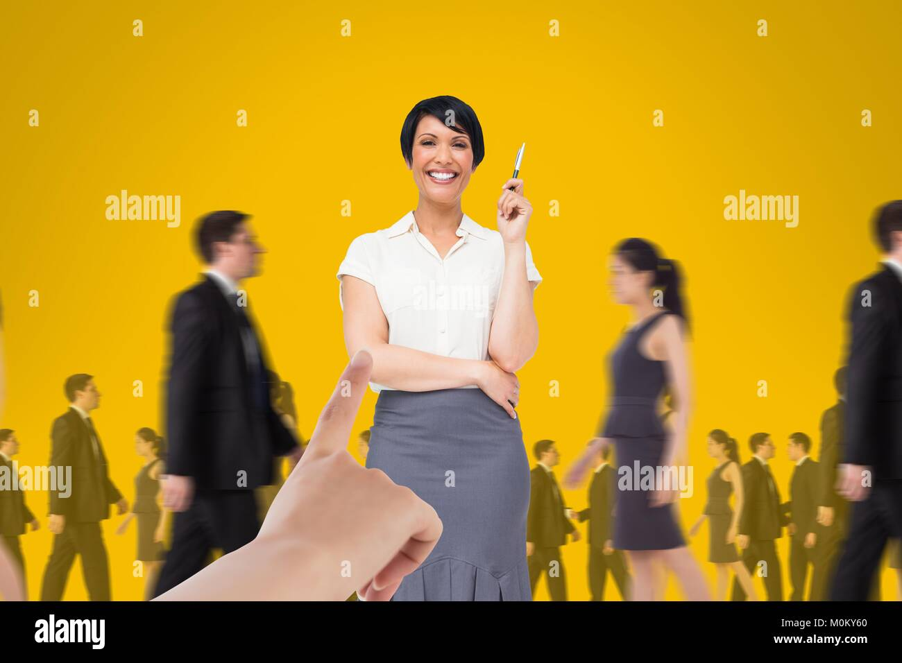 Hand choosing a business woman on yellow background with business people walking Stock Photo