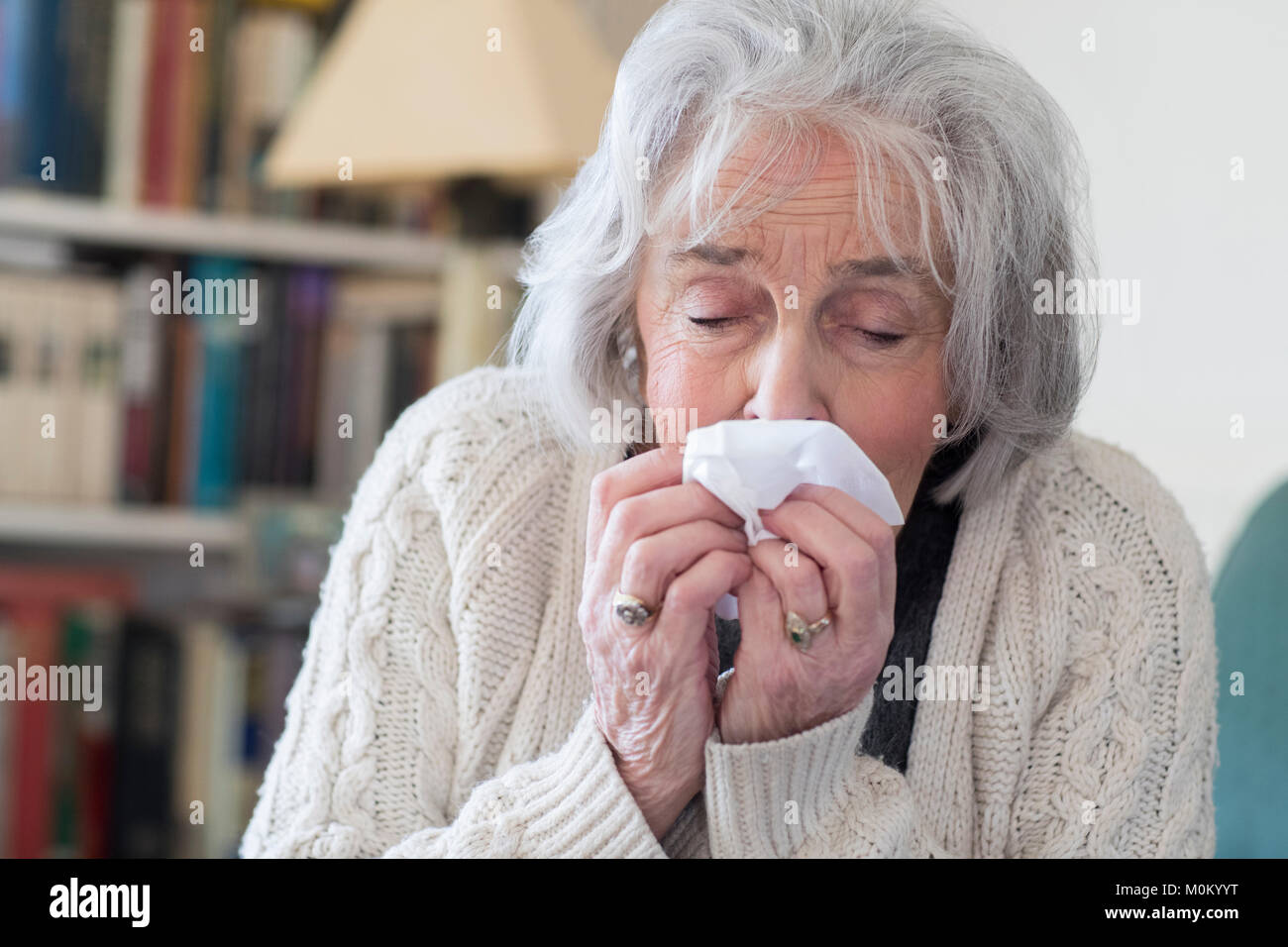 Senior Woman With Flu Blowing Nose At Home - Stock Image