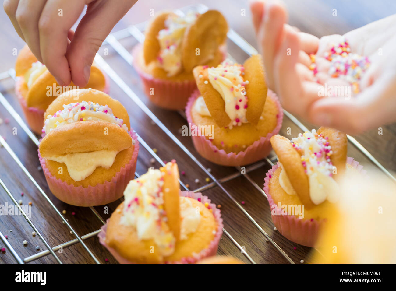 Close Up Of Girl In Kitchen Decorating Home Made Cupcakes - Stock Image