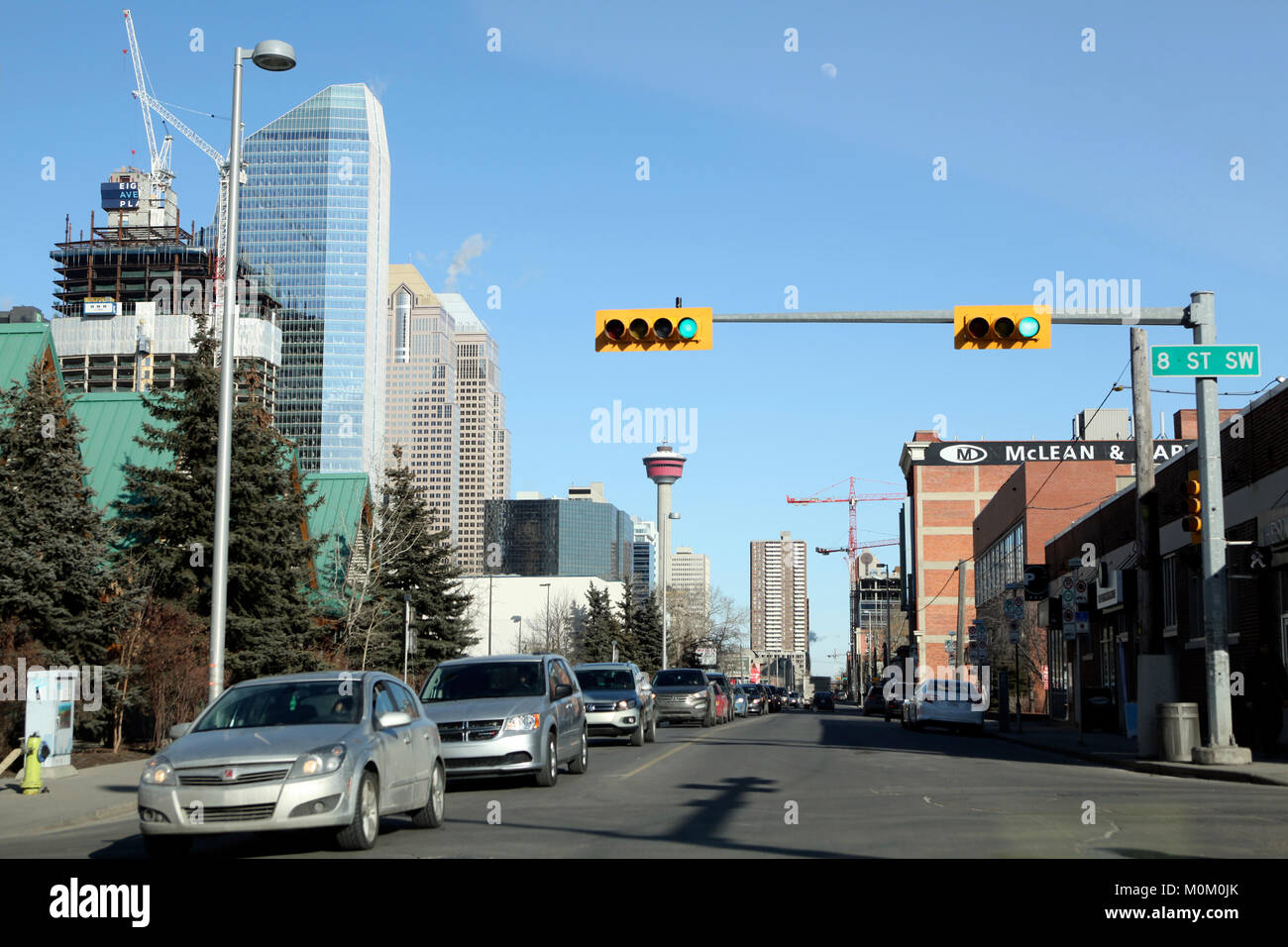 Cars rush on the green light on a sunny March day on a street crossing in Calgary, Alberta. Growing city enjoys Stock Photo