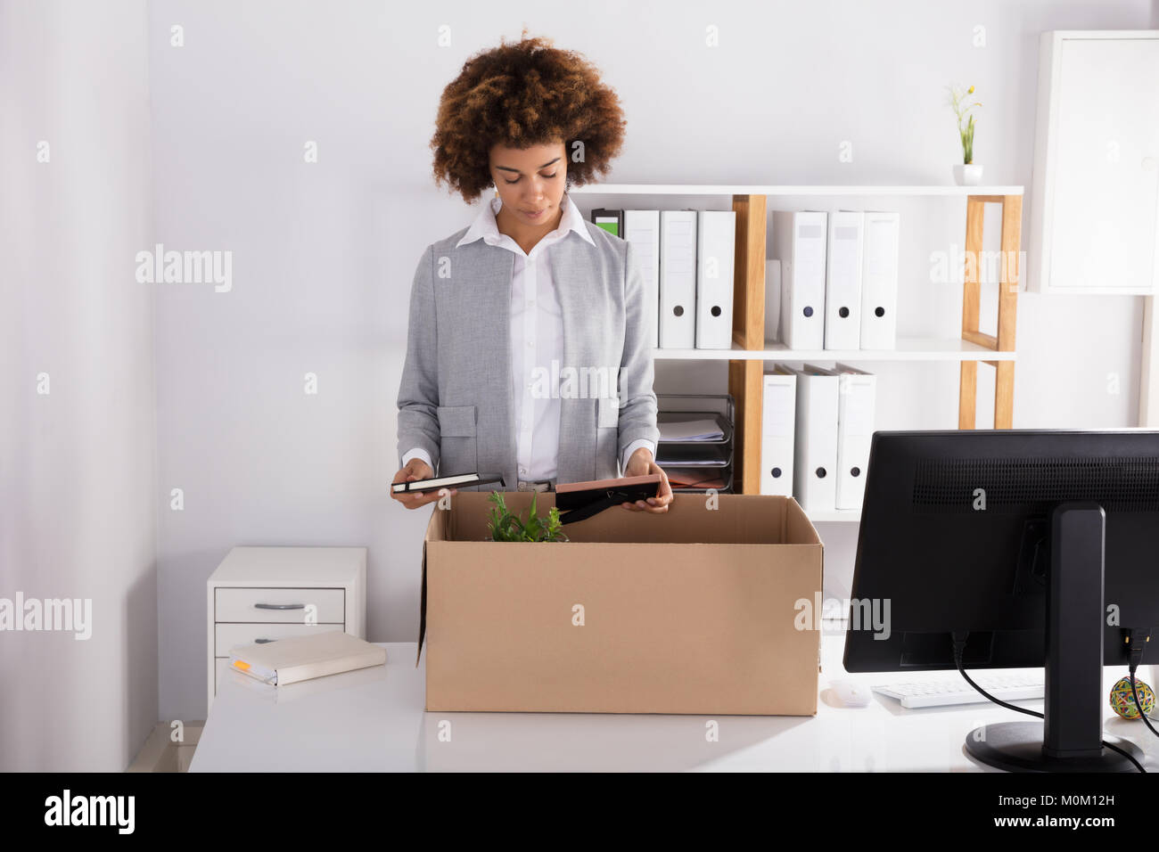 Sad Young Businesswoman Packing Her Belongings In Cardboard Box At Workplace - Stock Image