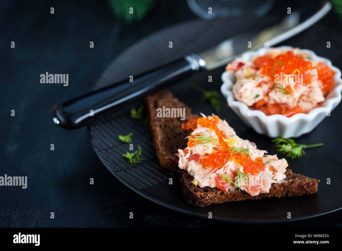 Salmon pate (rillettes) with red caviar served with sliced bread - Stock Image