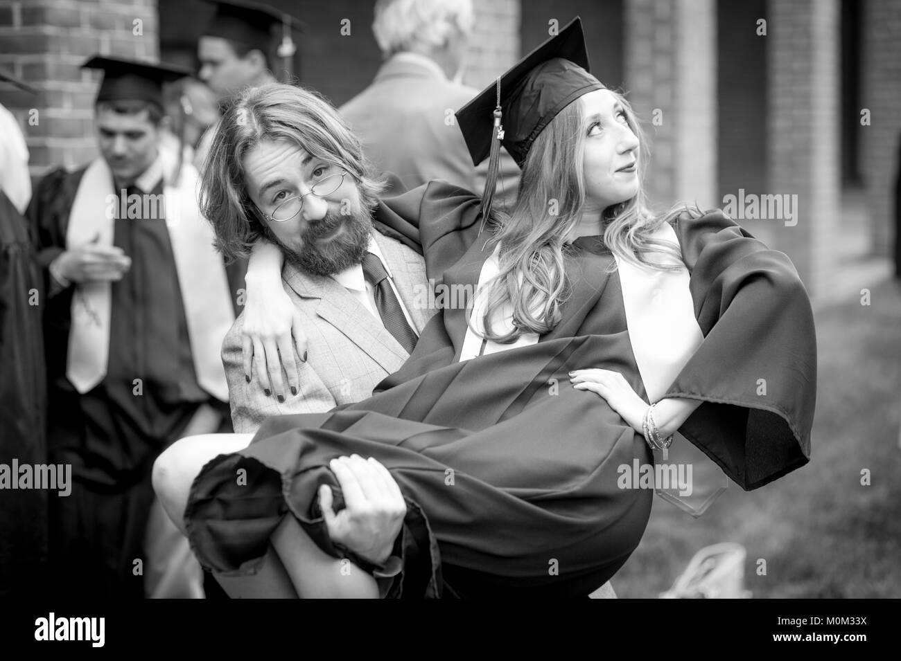 Young bearded man holds young female graduate in his arms, College Park, Maryland - Stock Image