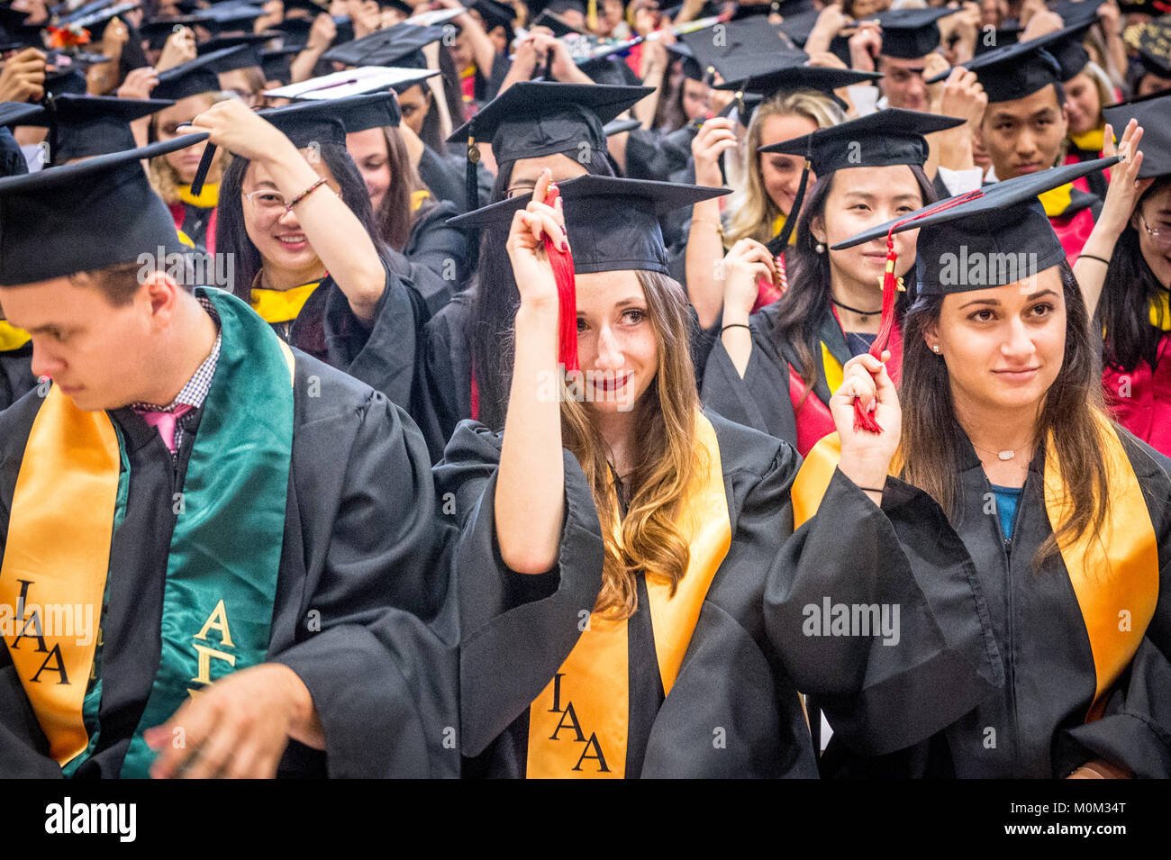 Group of young college graduates move their tassels on their graduation caps together, College Park, Maryland - Stock Image