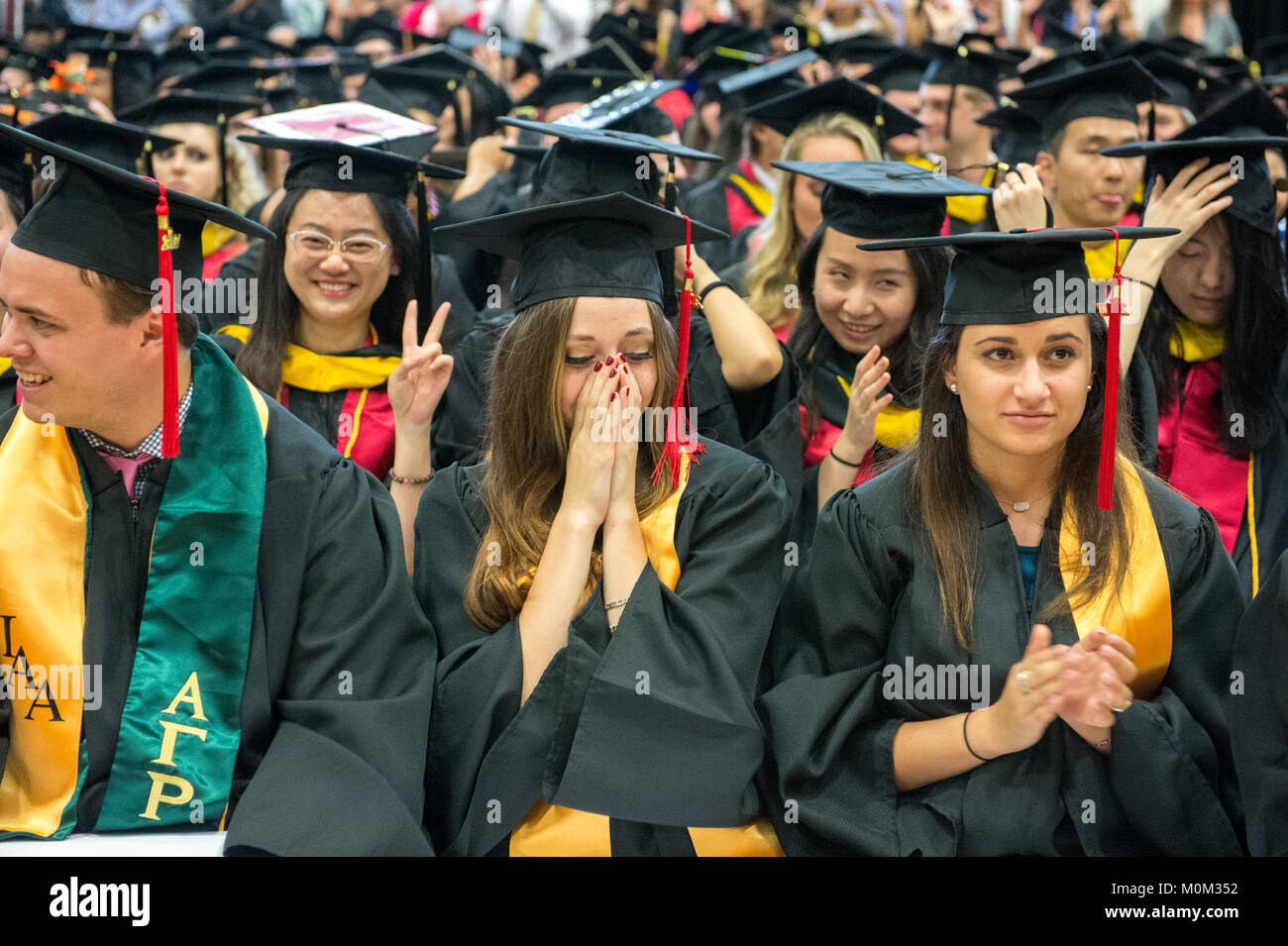 Young female graduate holds her face as she gets emotional amongst other college graduates, College Park, Maryland - Stock Image