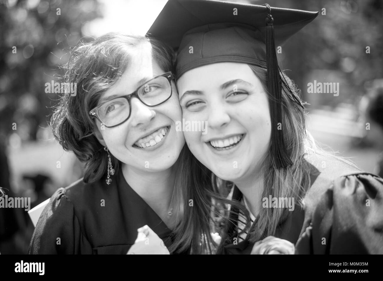 Two young female college graduates hug and smile with one another, Swarthmore, Pennsylvania - Stock Image