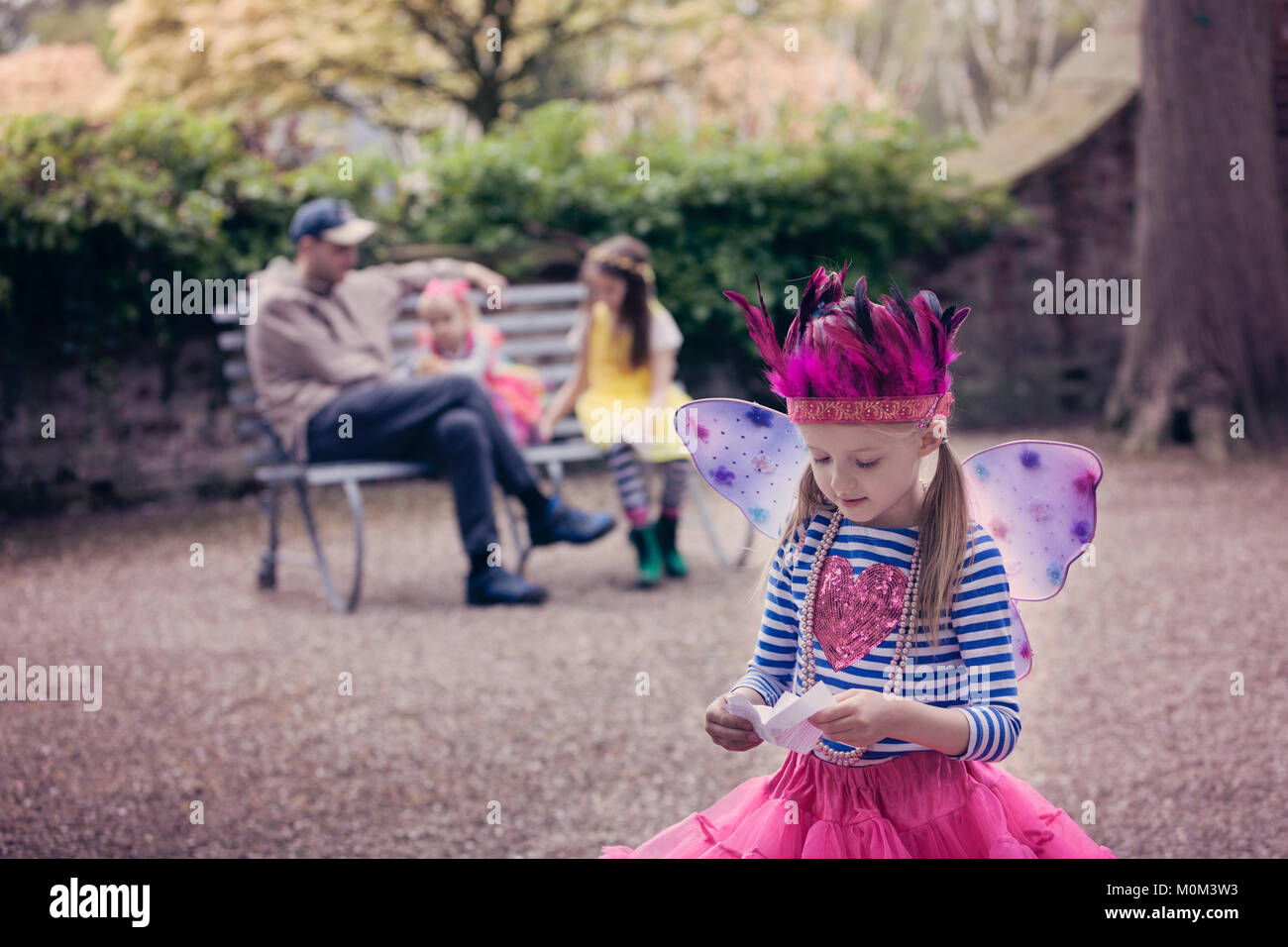 Girl in fairy costume, reading a letter, with family in the background - Stock Image