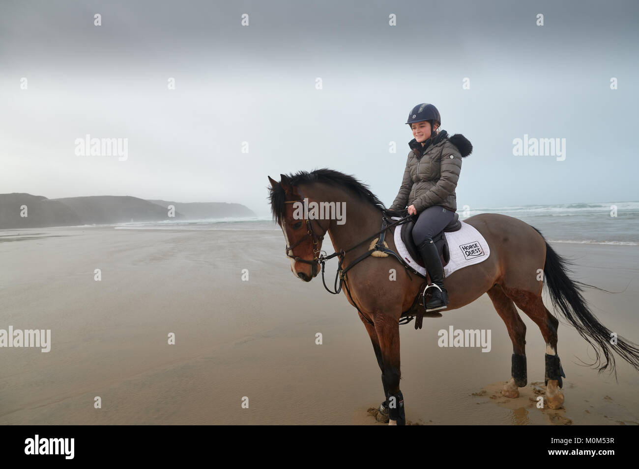 Horse rider riding away from the camera down the beach at low tide. Black & white image, with an obscured horizon - Stock Image