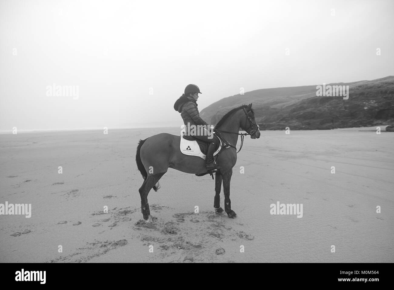 Horse rider stationary looking up the beach, Atmospheric shot taken in Black & white. Cliffs beach and mist - Stock Image