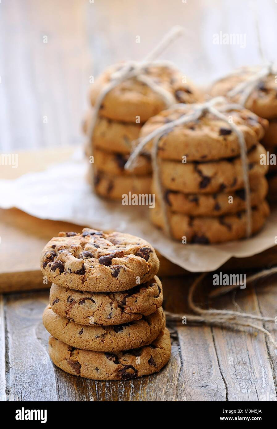 Close-up of several piles of chocolate cookies on wooden table. - Stock Image