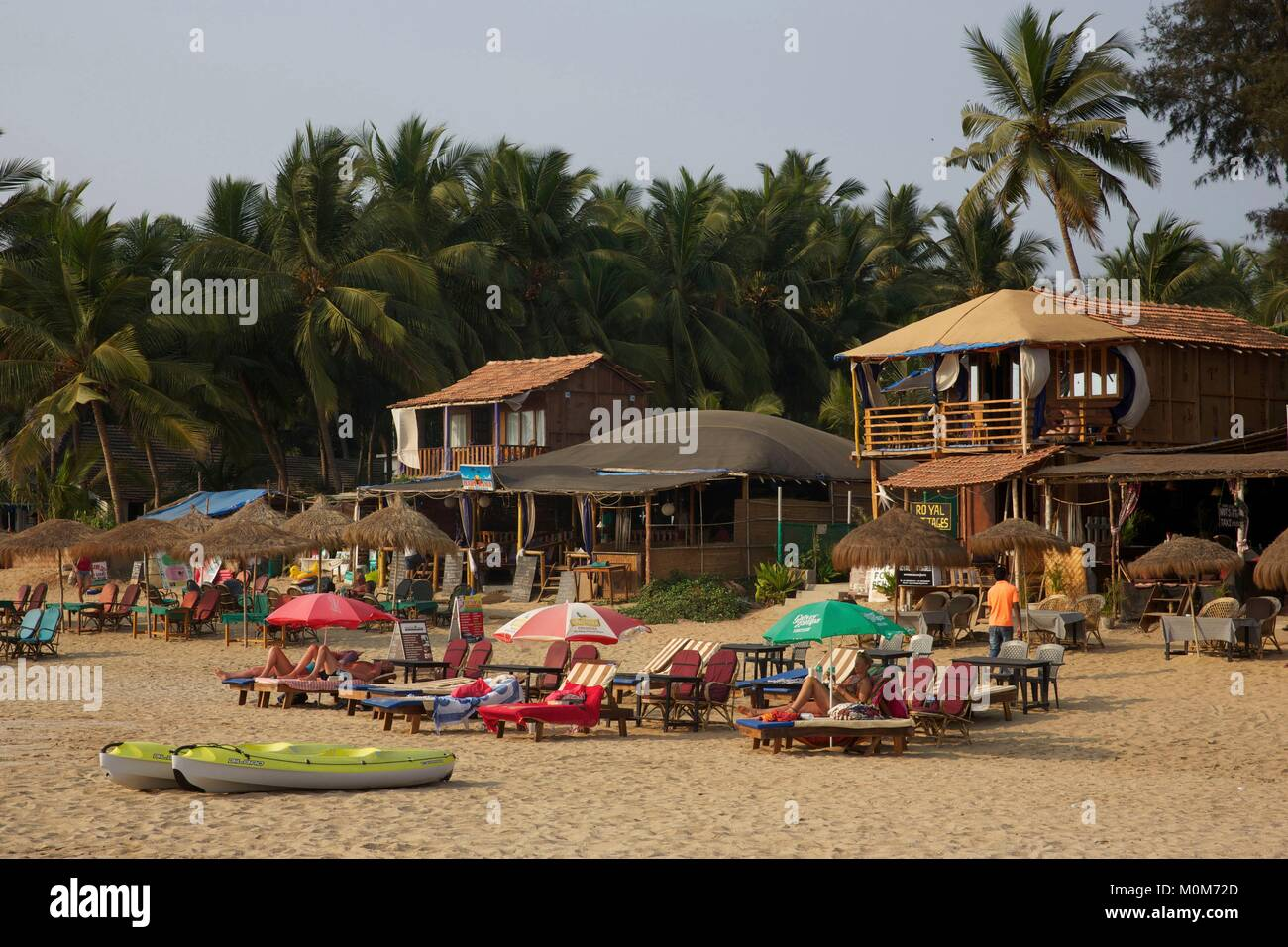 India,Goa,Patnem beach,tourists lying on deckchairs in the golden sand beach lined with coconut trees,near Palolem - Stock Image