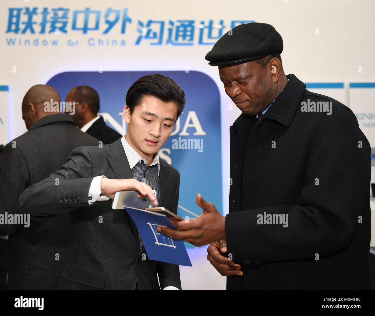 (180123) -- BEIJING, Jan. 23, 2018 (Xinhua) -- A staff member shows the Xinhua News App to a foreign guest, in Beijing, Stock Photo