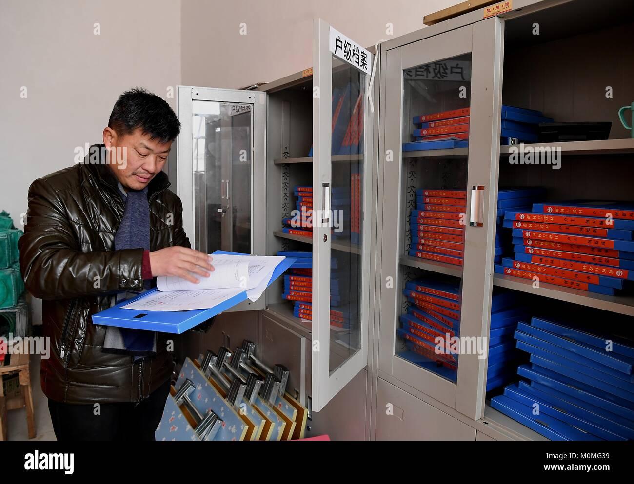 (180123) -- ZHENGZHOU, Jan. 23, 2018 (Xinhua) -- First secretary Han Yunan of Qianhe Village reads on files of poor Stock Photo