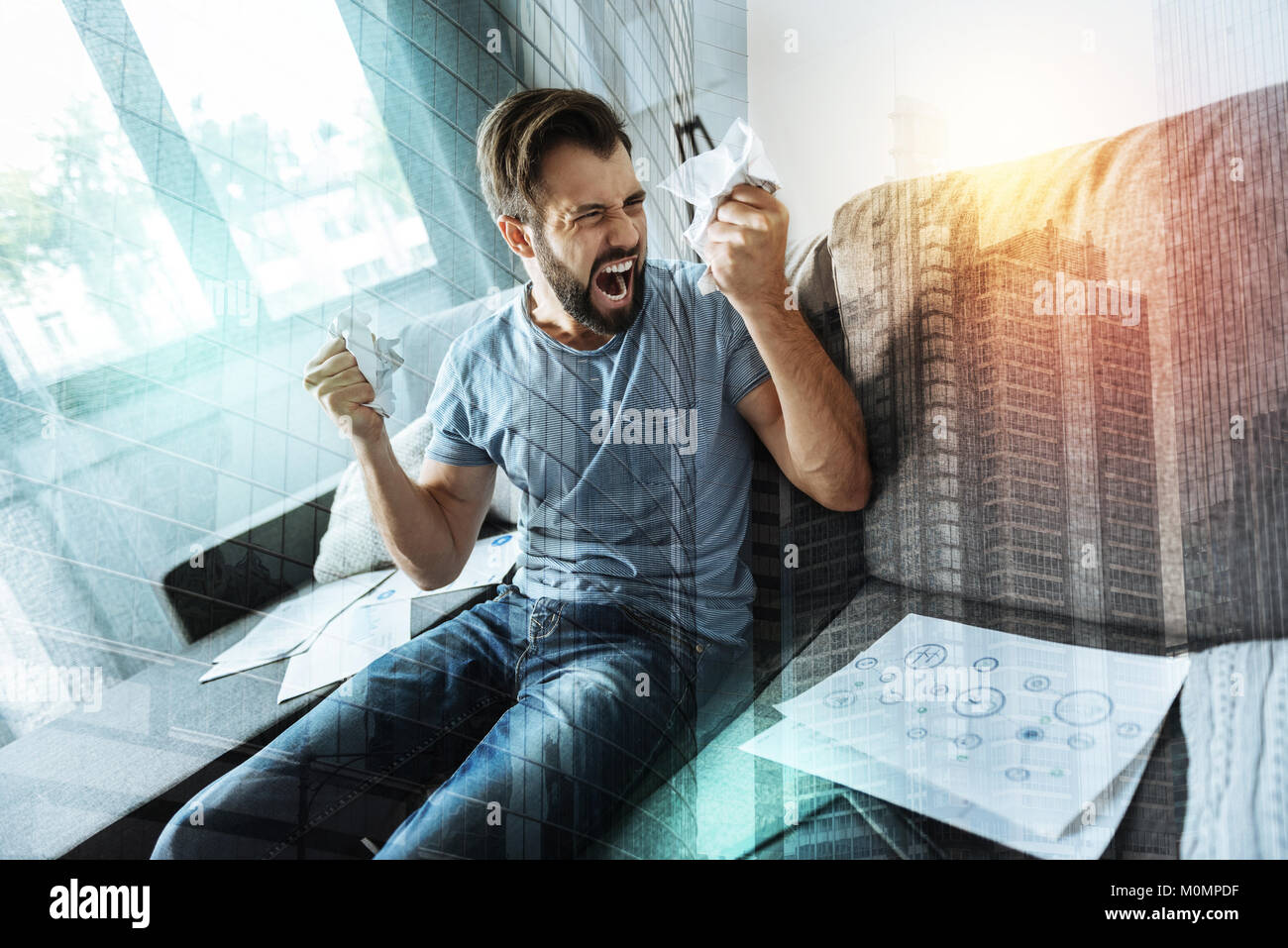 Angry frustrated man looking at paper and screaming. - Stock Image