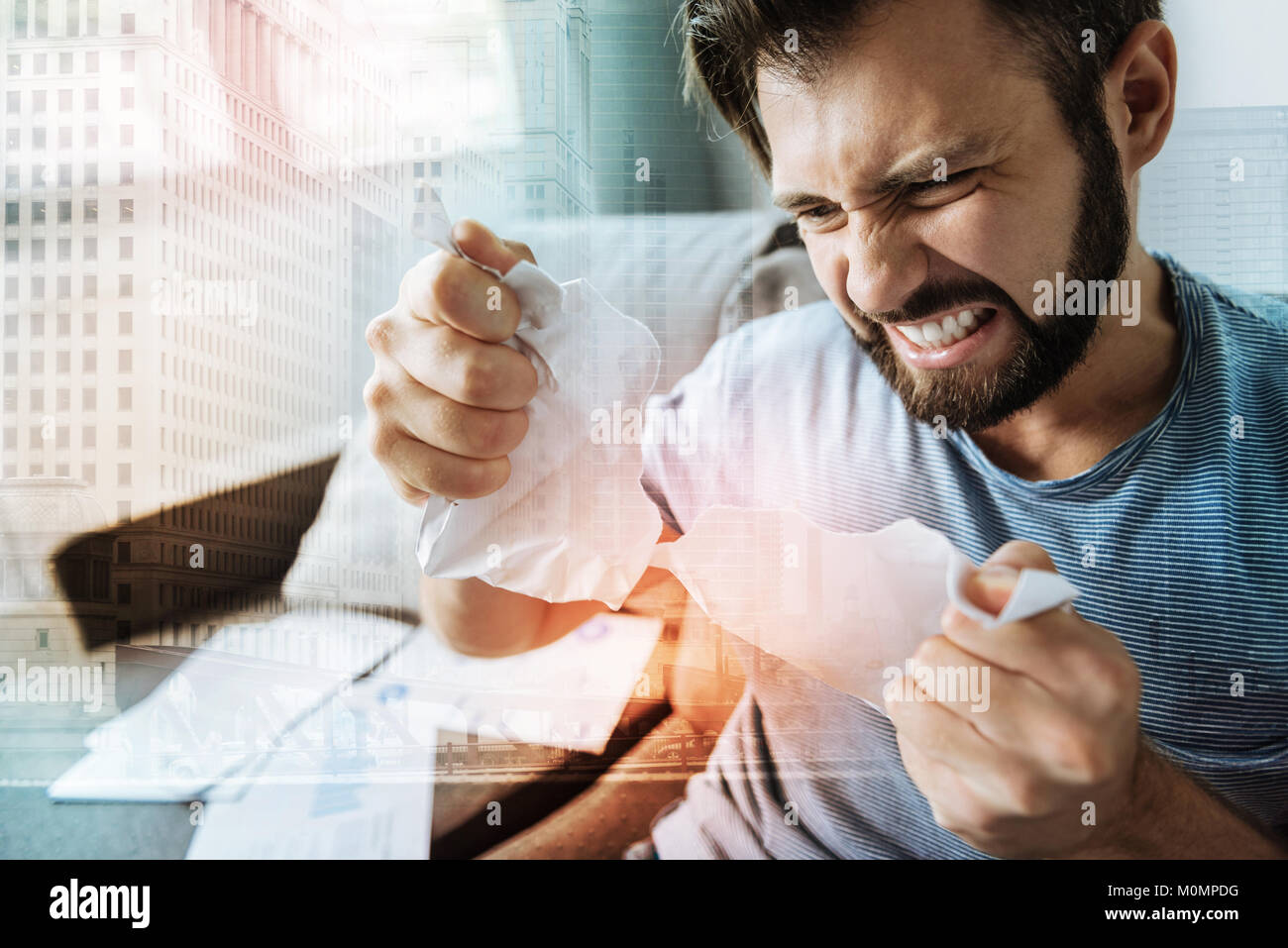 Angry stressful man tearing the paper and merging. - Stock Image