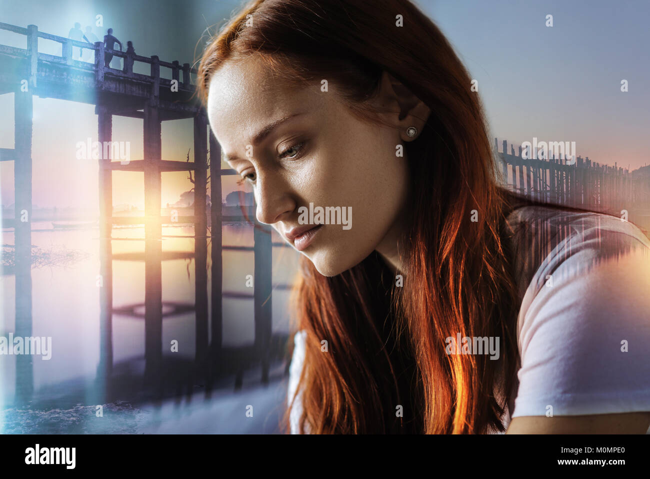 Pretty deep woman looking down and thinking. - Stock Image