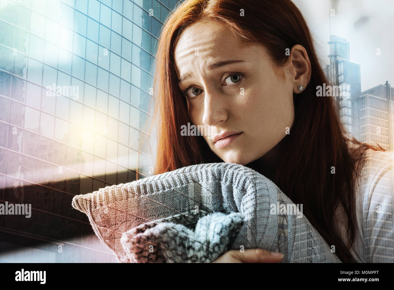 Lonely stressful woman hugging the pillow and looking straight. - Stock Image