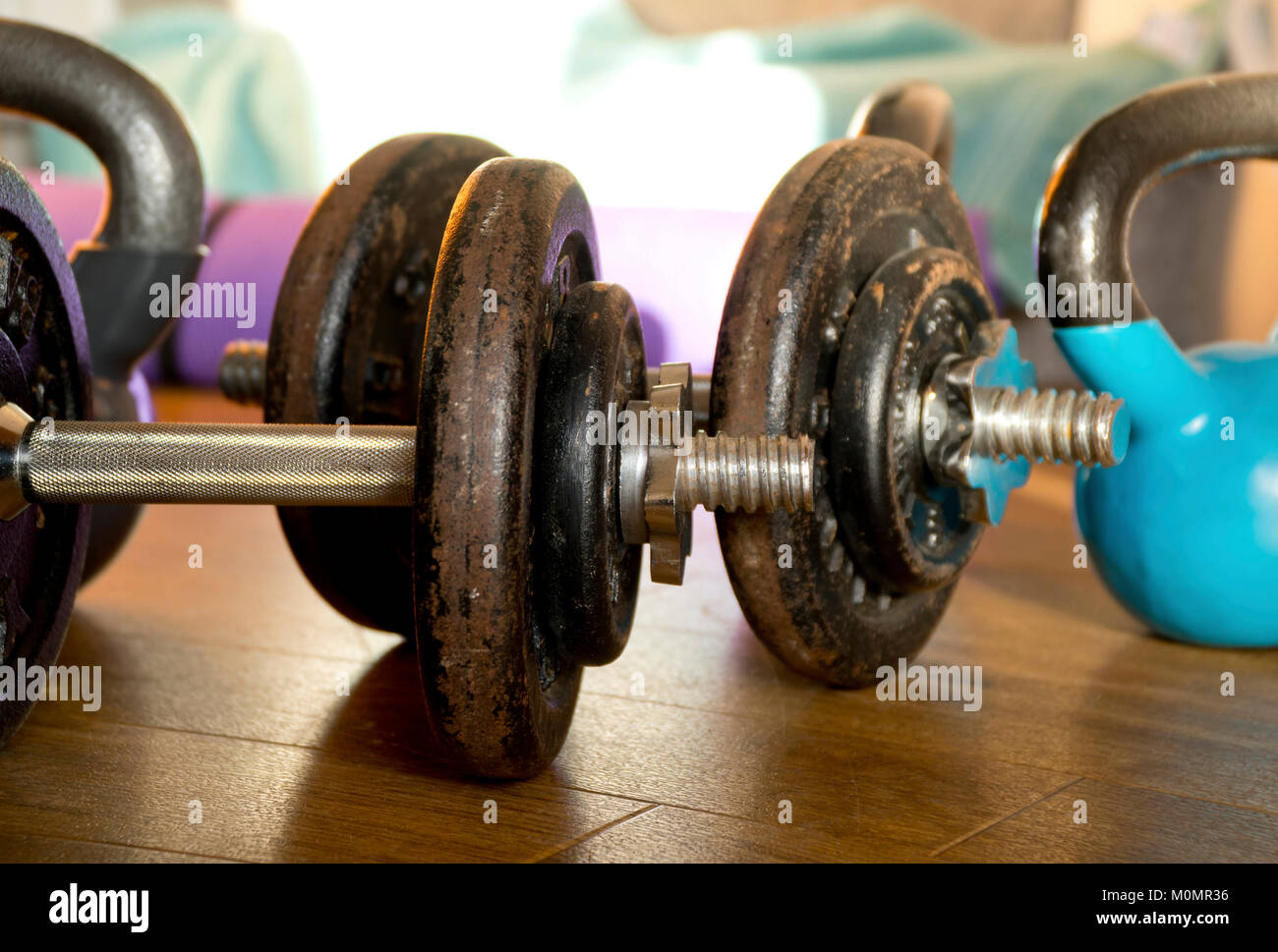 Dumbbells and kettlebells on a wooden floor. - Stock Image