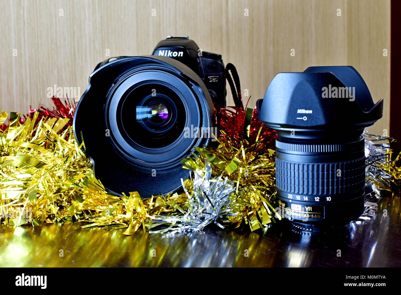 Nikon DSLR D80 and battery pack and Lenses on display and Christmas decorations as well Stock Photo