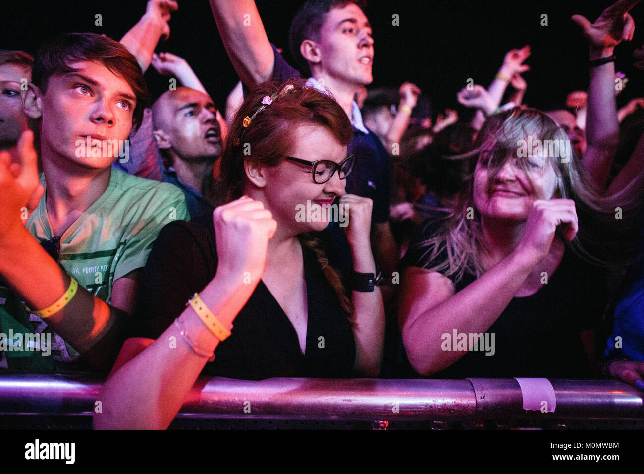 Energetic festival goers and music fans go crazy at a live concert