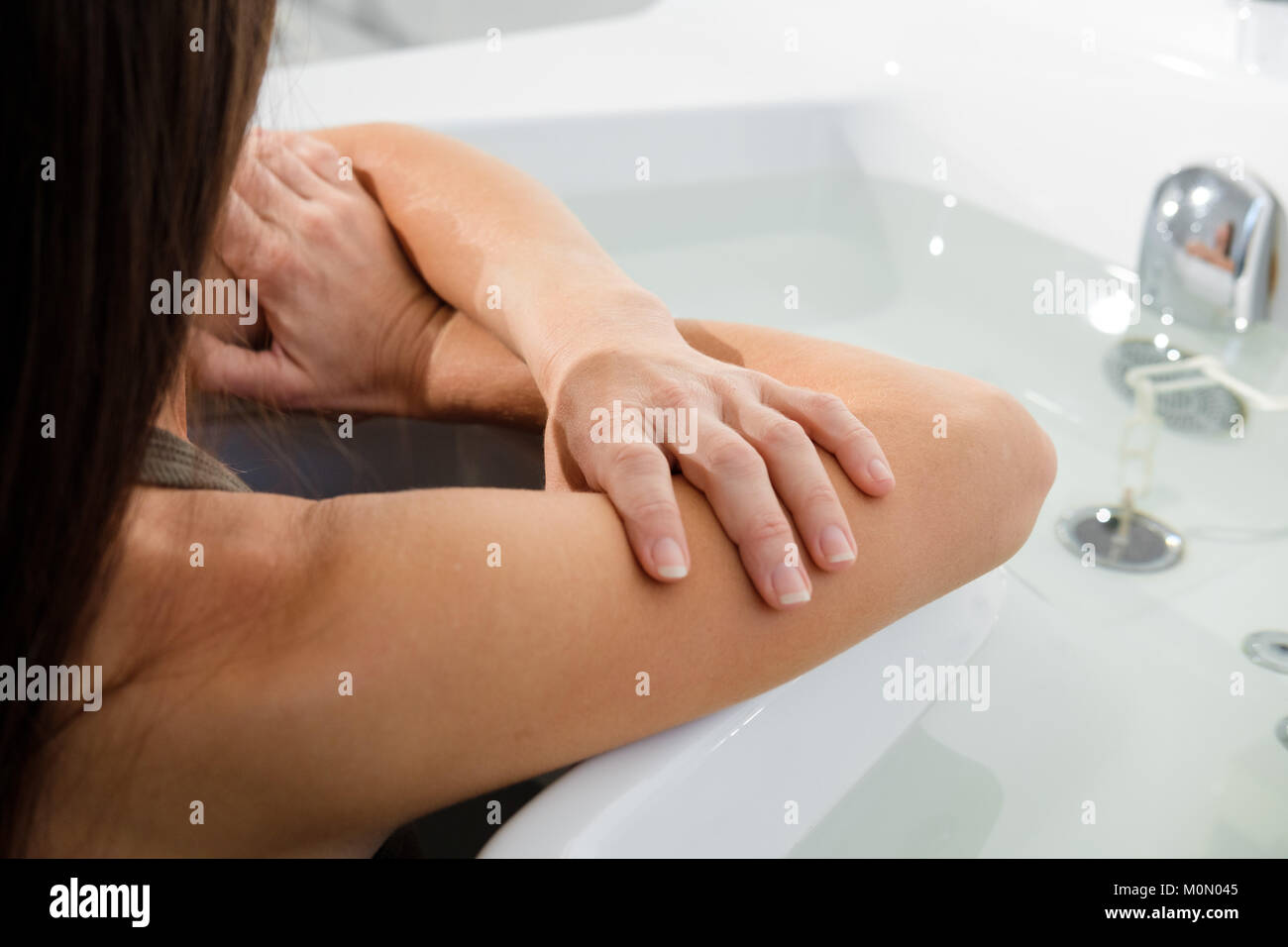 woman relaxing receiving water procedures in spa salon. female patient on hydrotherapy. Soft focus on hands. Copy - Stock Image