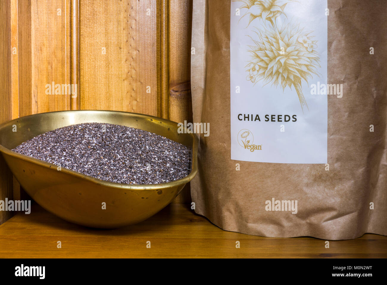 Chia seeds (salvia hispanica). Organic, uncooked, high in protein, vegan, superfood. In a packet and a weighing - Stock Image
