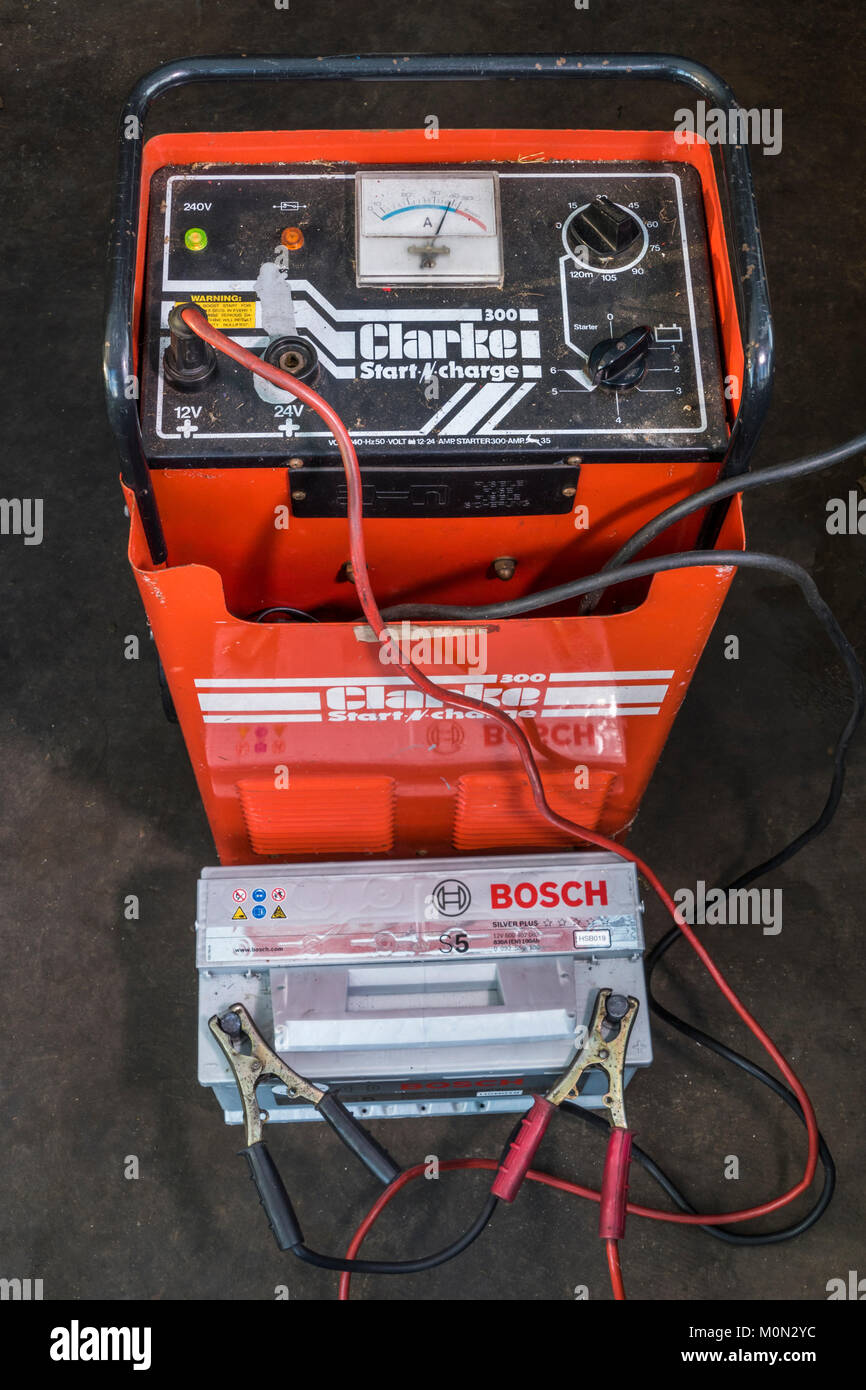 On charge: a flat 12 volt car battery connected to, and receiving a charge from, an industrial, heavy duty, Clarke - Stock Image