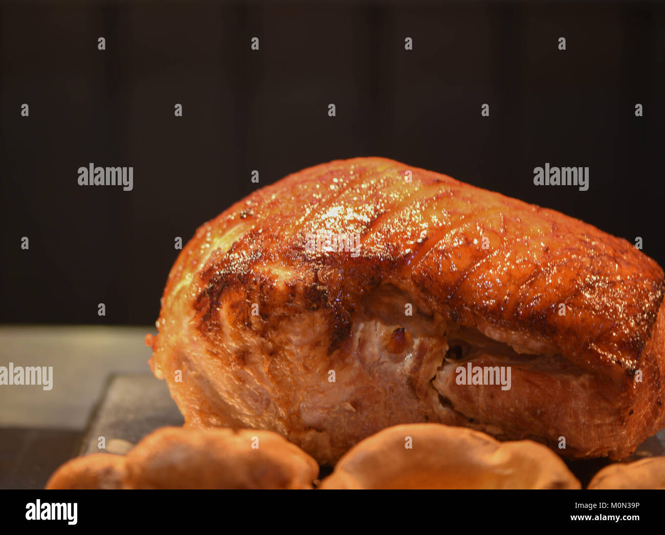 close up food photography image of a cooked and resting roast dinner joint of meat of a gammon or pork with a dark - Stock Image