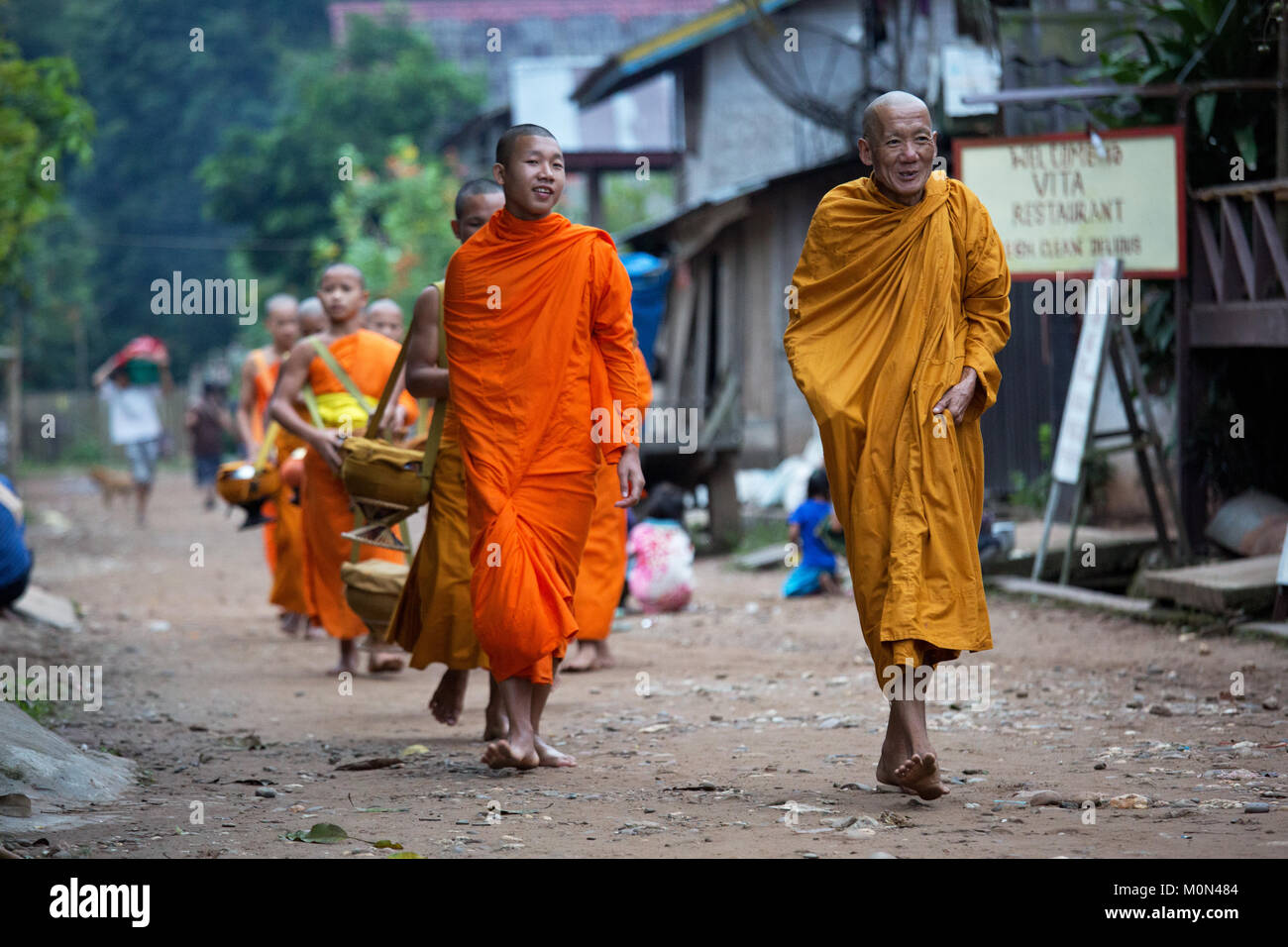 Monks walking back to Temple after collecting alms in the early morning in Muang Ngoi, Northern Laos - Stock Image