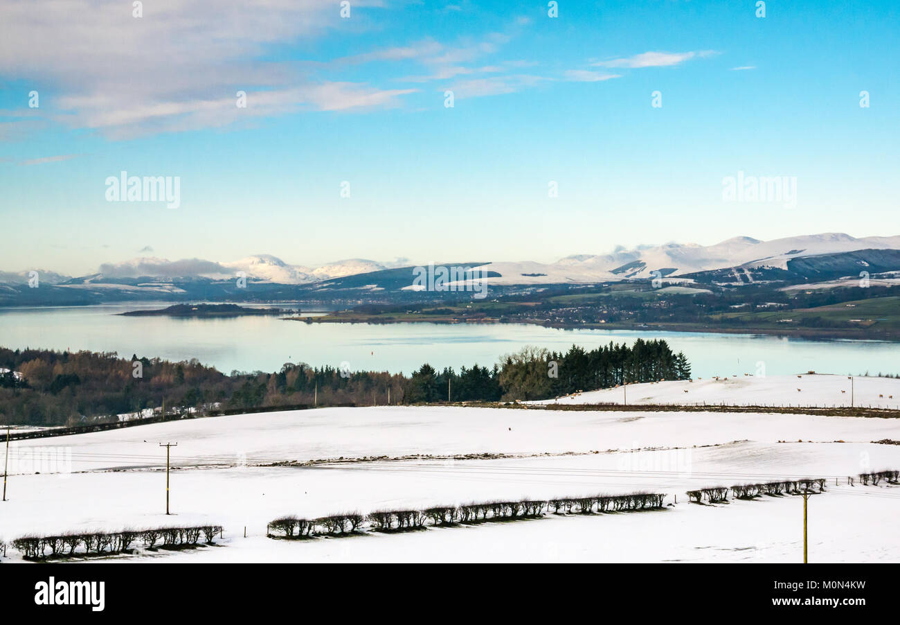 Winter scene of Clyde River to Gare Loch from hill above Langbank, with snow covered mountains, blue sky and calm - Stock Image