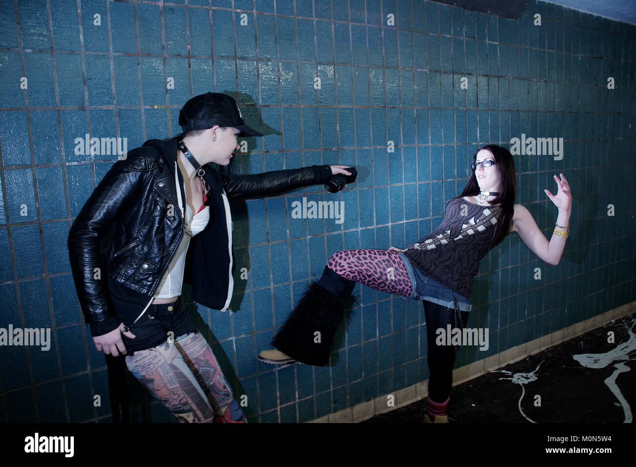 One girl shooting another with a strobe light in a subway - Stock Image