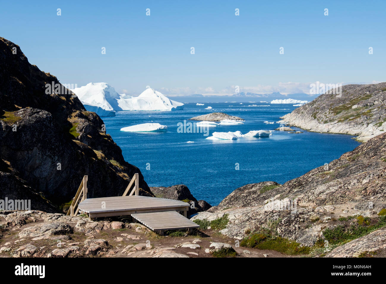 Steps down to boardwalk with icebergs from Ilulissat Icefjord drifting into Disko Bay. Nakkaavik viewpoint, Ilulissat - Stock Image
