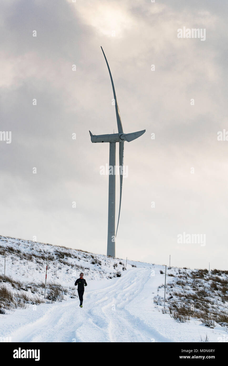 Man running in snow beside  wind turbine at Whitelee Windfarm in East Renfrewshire operated by Scottish power, Scotland, - Stock Image