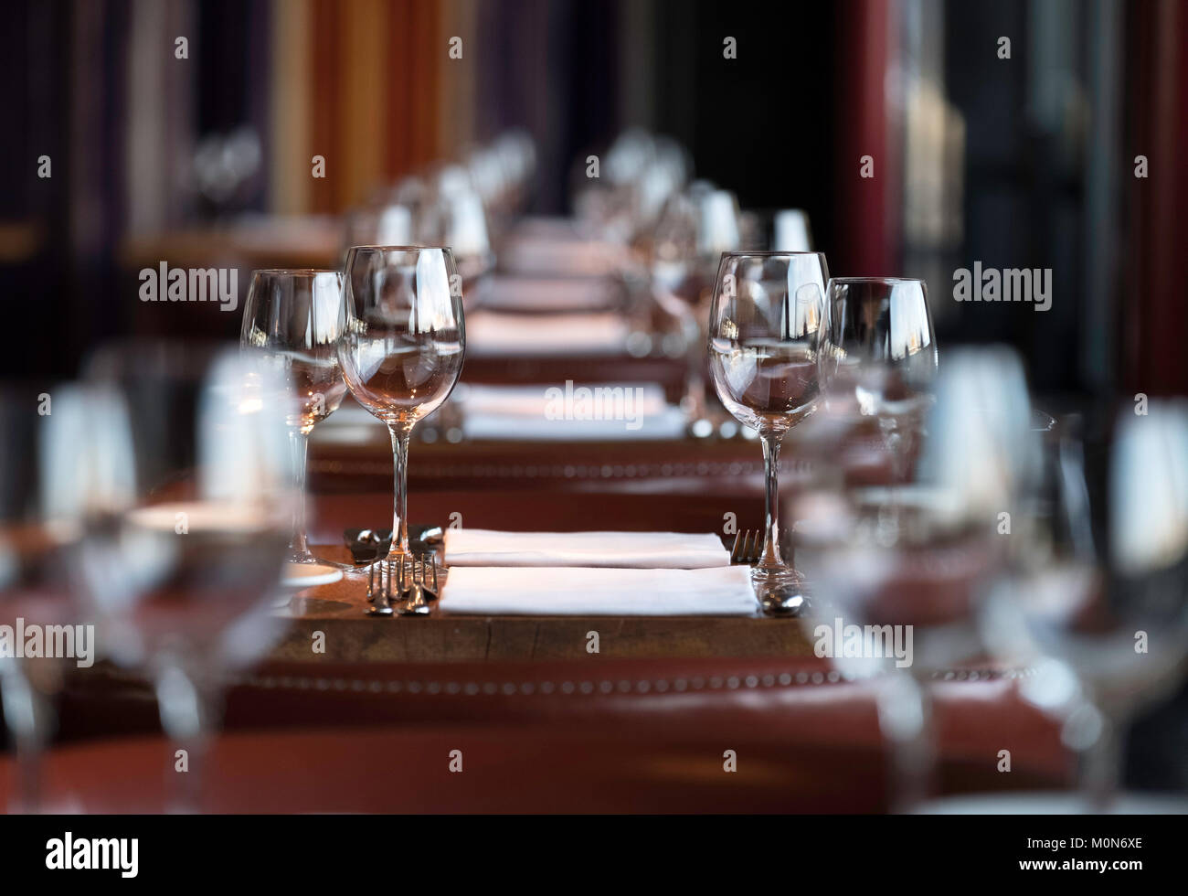 View of row of wine glasses of tables at a restaurant - Stock Image