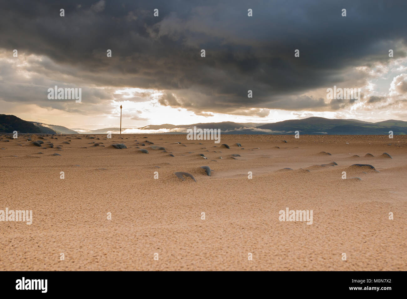 Scary dark storm clouds make a foreboding appearance in the skies over Ynyslas Estuary Beach. Sunlit background - Stock Image