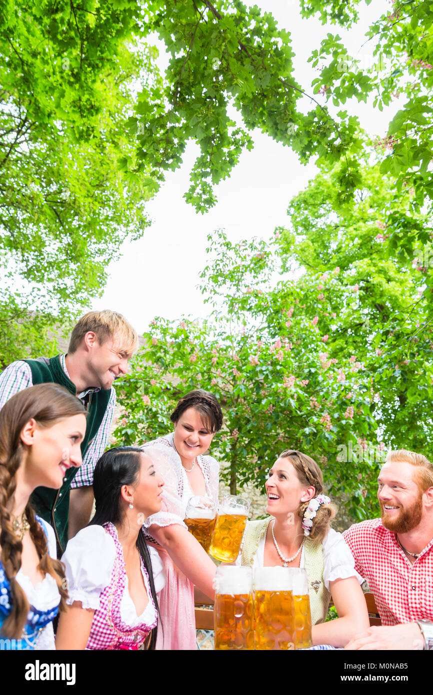 Waitress serving beer in beer garden - Stock Image