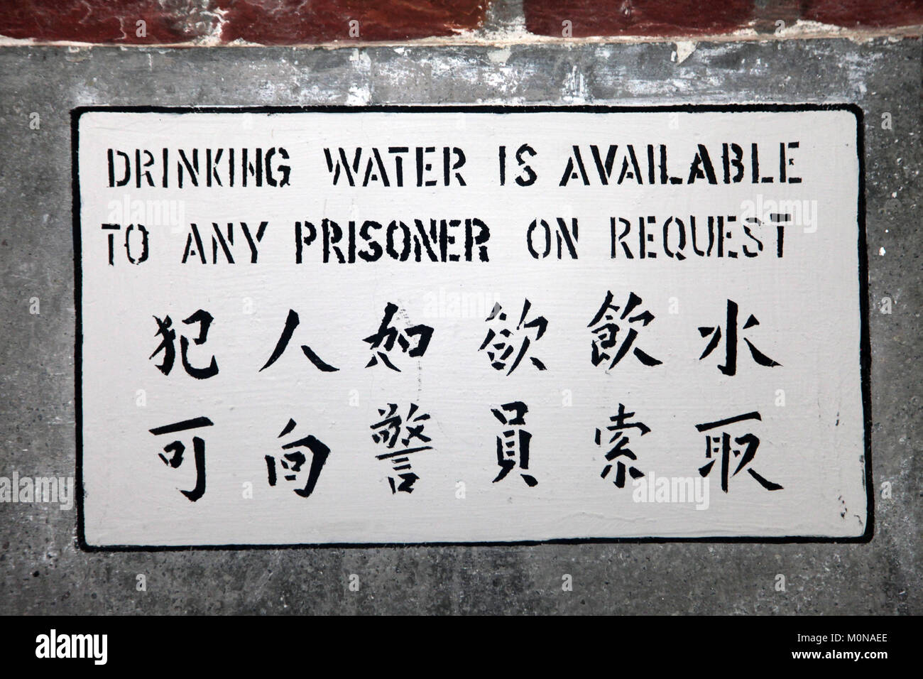Indication Sign written on the wall in a prison or jail in english and chinese Stock Photo