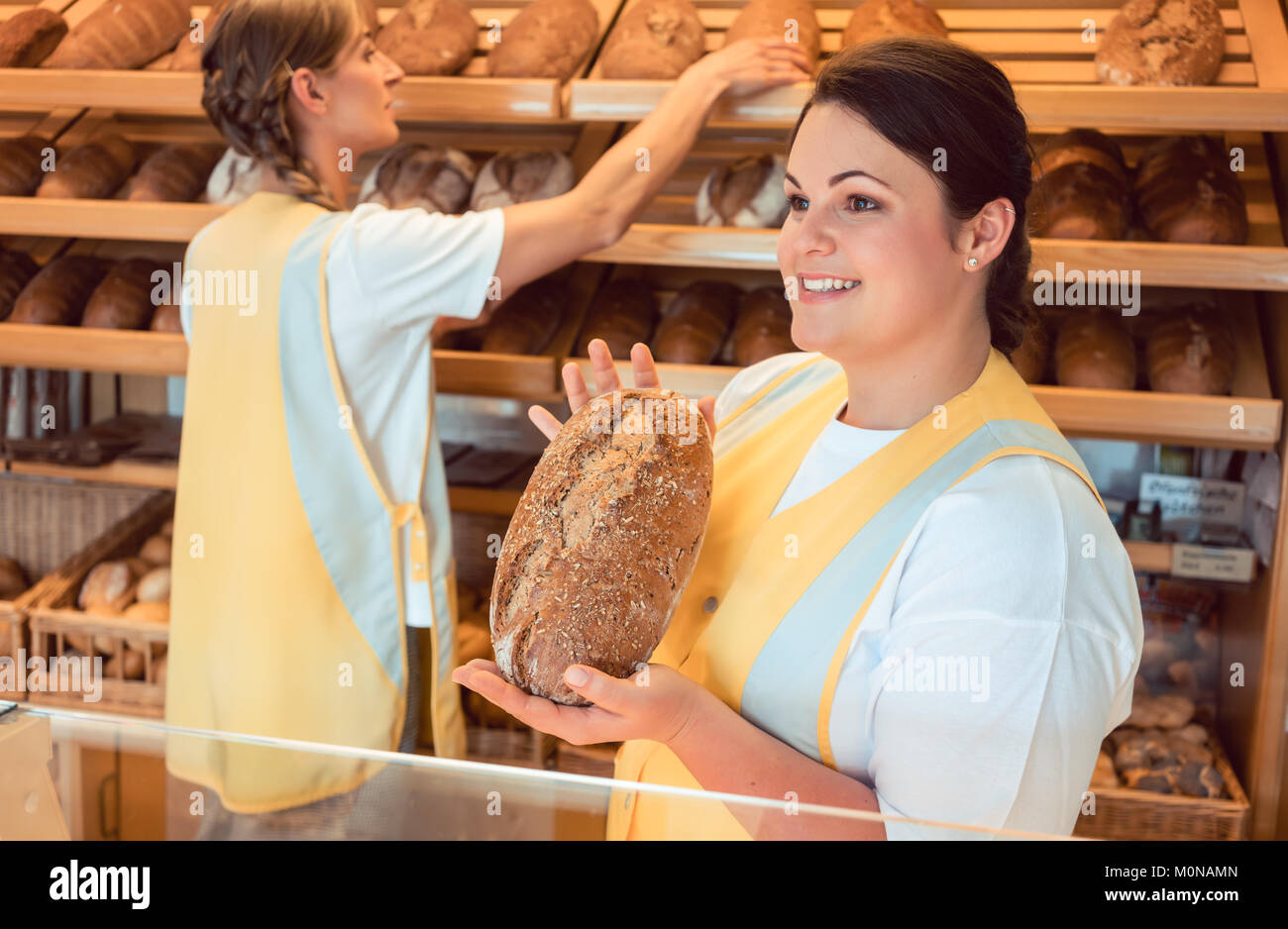 Two salesladies selling bread and other products in bakery shop - Stock Image