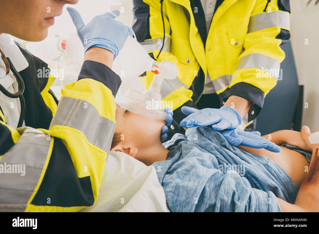 Emergency doctor giving cardiac massage for reanimation in ambul Stock Photo