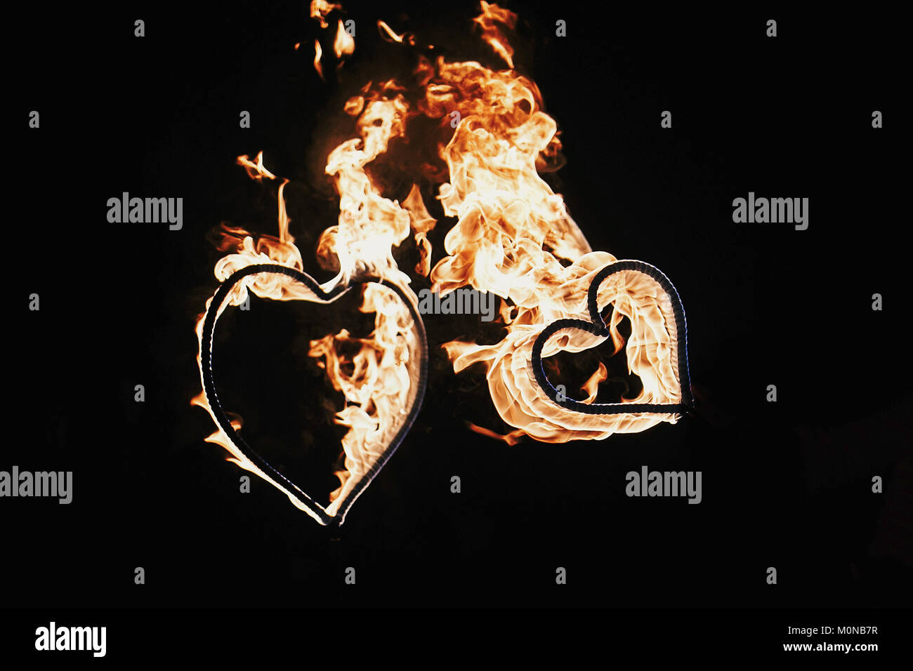 happy valentine's day card. two hearts shaped fireworks on black background, fire show in night. bengal fire burning heart. space for text. wedding or Stock Photo