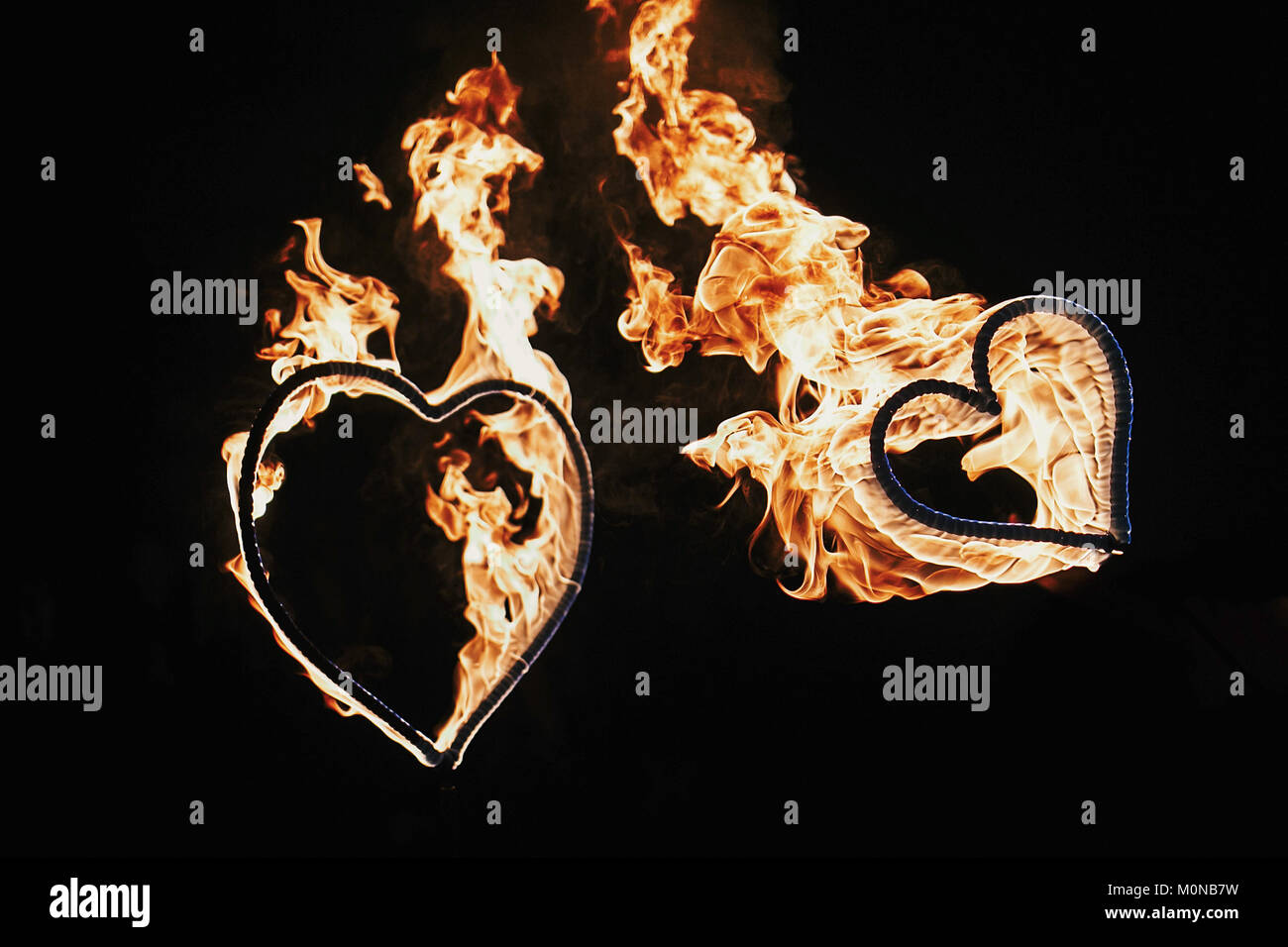 two hearts shaped firework on black background, fire show in night. happy valentine's day card. bengal fire burning heart. space for text. wedding or  Stock Photo