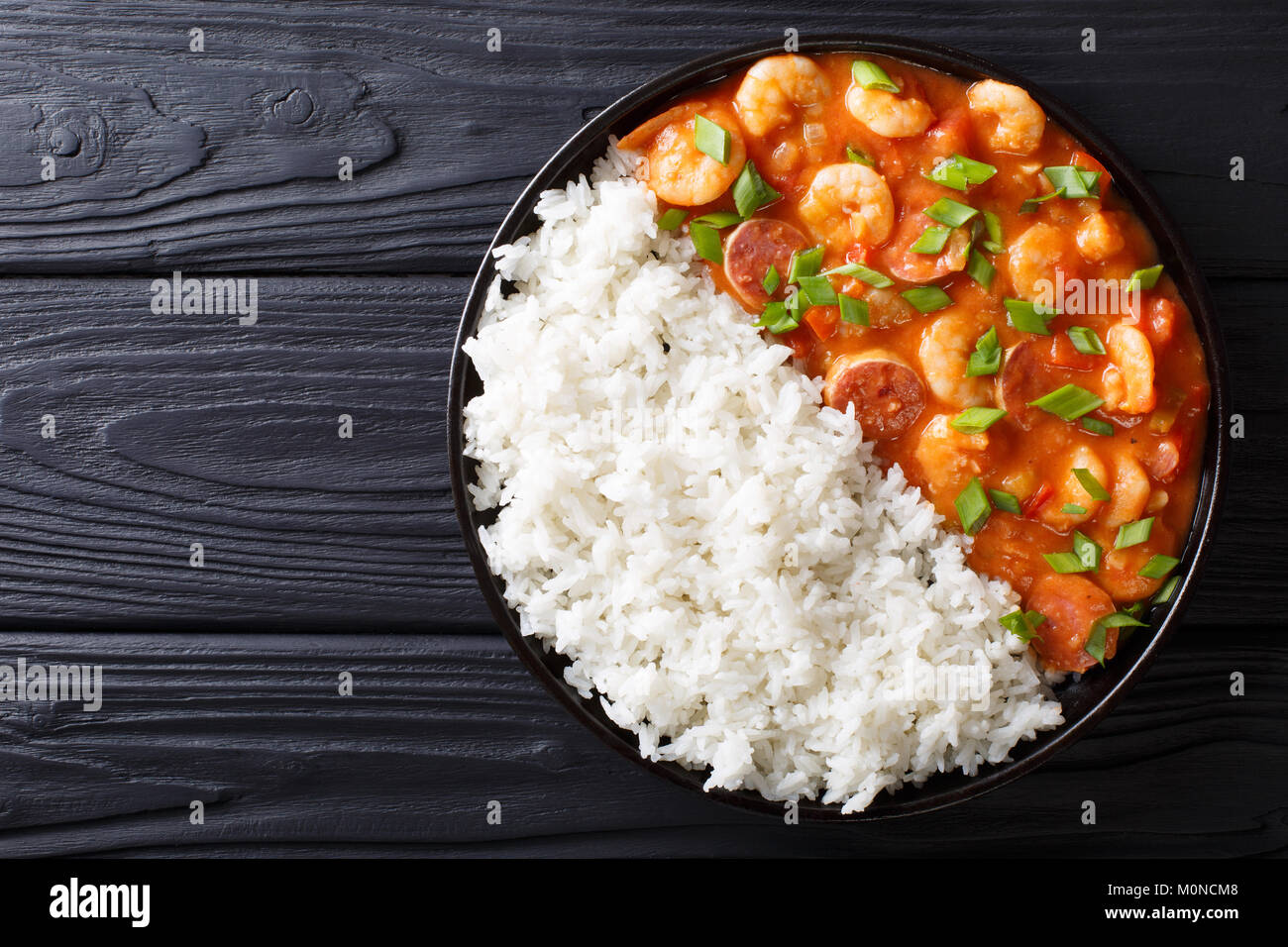 Delicious gumbo with prawns, sausage and rice on a plate on the table. horizontal top view from above - Stock Image