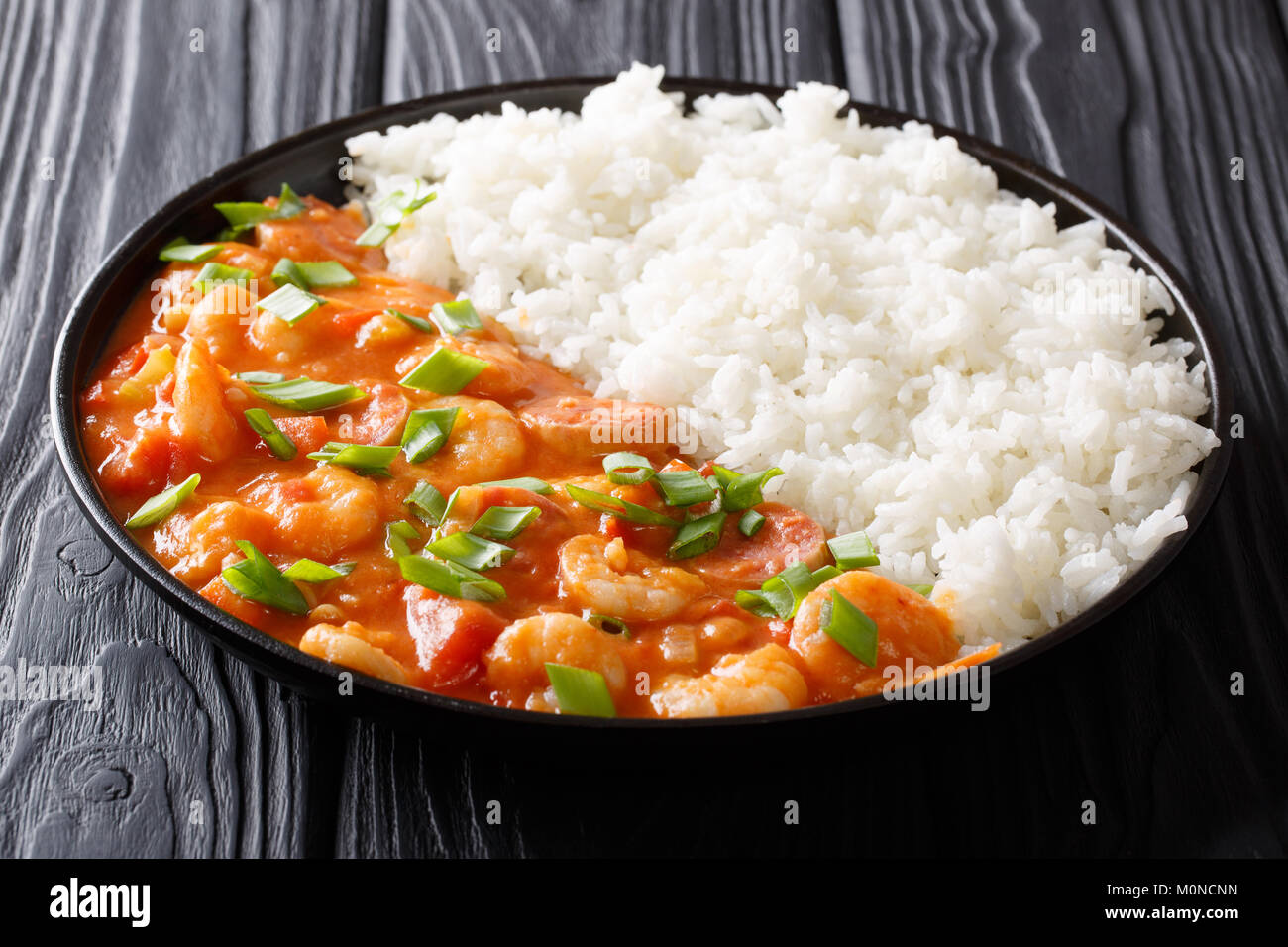 American cuisine: spicy gumbo with prawns, sausage and rice close-up on a plate on a table. horizontal - Stock Image