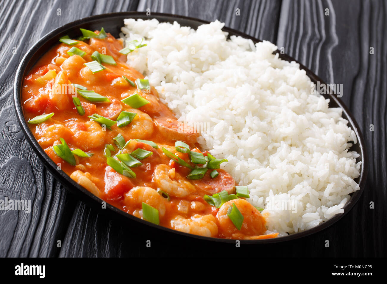 Creole food: spicy gumbo with prawns, sausage and rice close-up on a plate on a table. horizontal - Stock Image