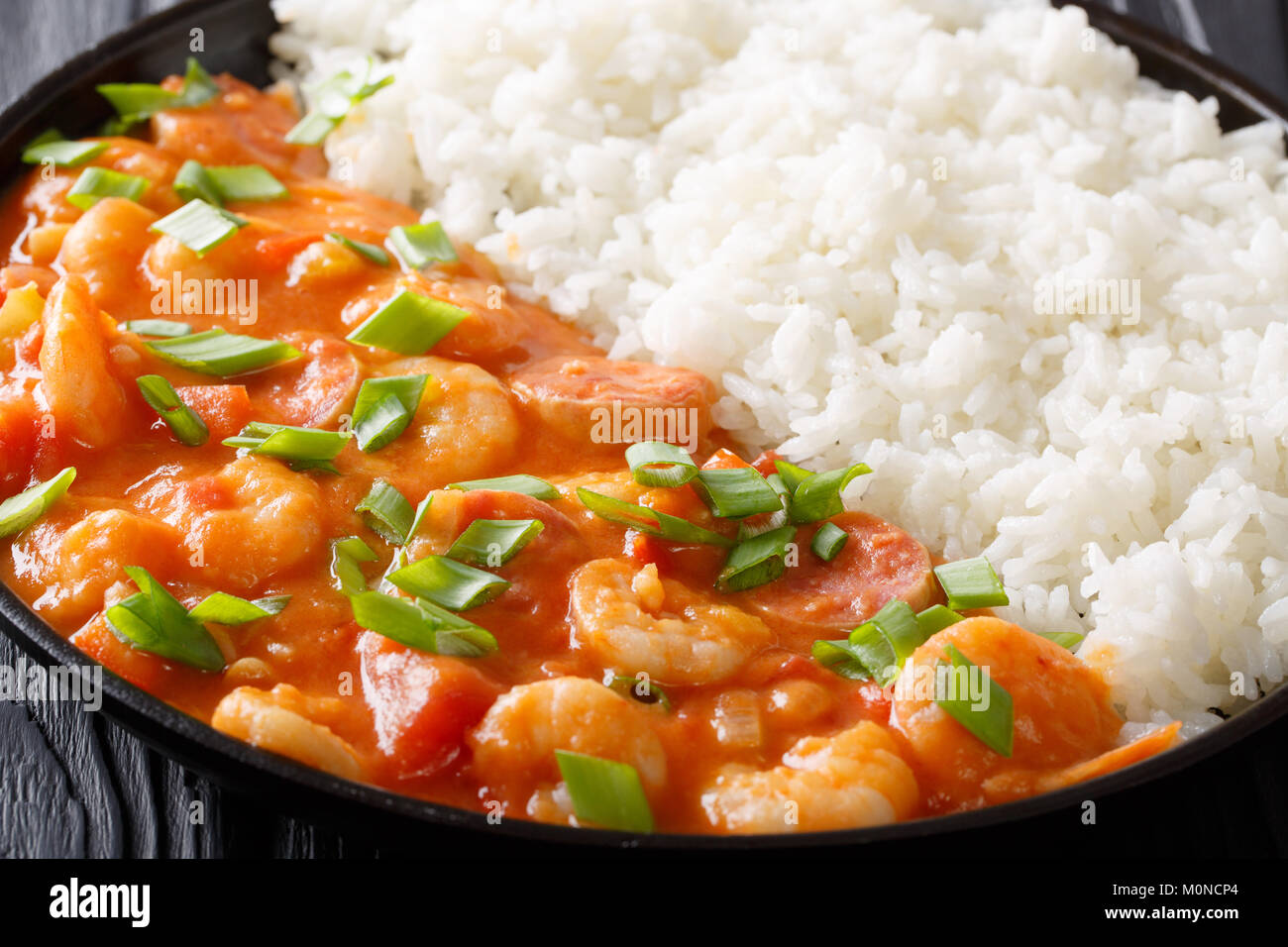 Delicious gumbo with prawns, sausage and rice macro on a plate on the table. horizontal - Stock Image